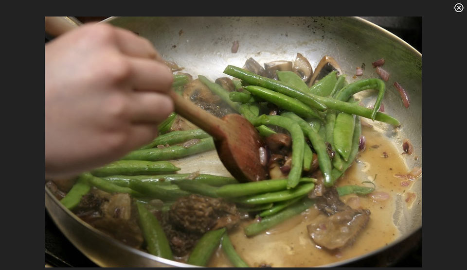 Screenshot of video, a hand cooking green beans in sauce